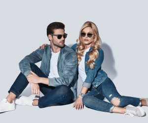 Romantic couple. Beautiful young couple in denim wear bonding while sitting against grey background